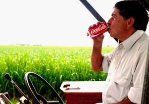 Gerry Deguara drinks a Coke while driving a tractor